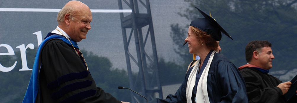 An adult student shakes hands with Dr. Hillkirk at Commencement