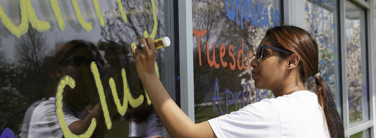 Student in the unity club painting the windows