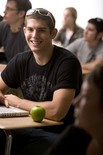student at desk with green apple