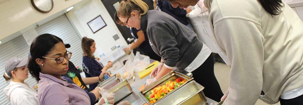 Students volunteer in a kitchen, preparing meals