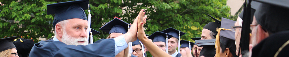 Adult Learner high fiving Faculty after Graduation