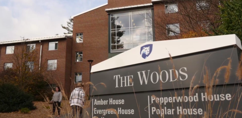 """Shot of """"The Woods"""" sign outside the residence halls on campus"""
