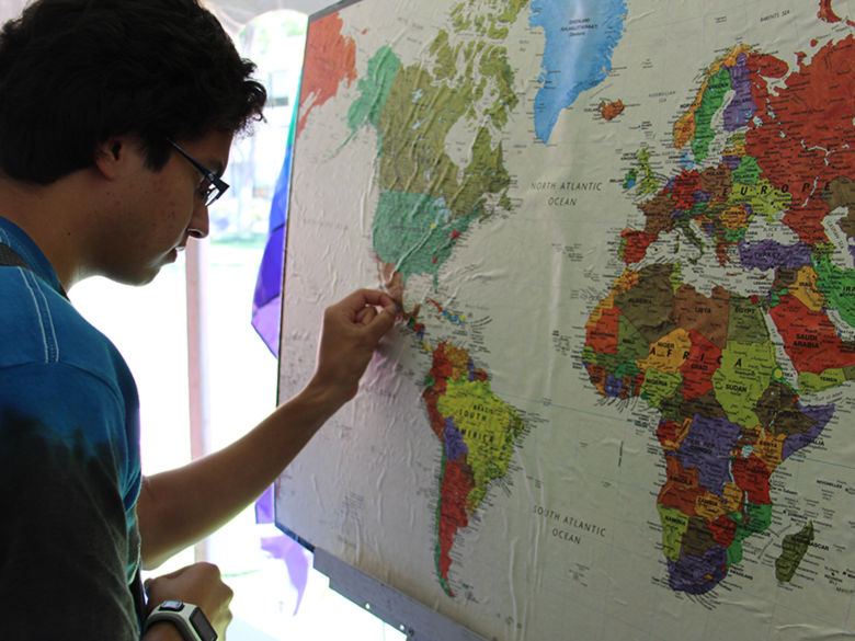 Students marking the globe with where they are from or where they have visited