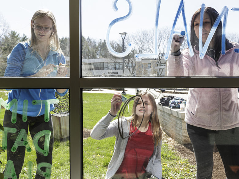 Students working on writing messages on Thun Library windows