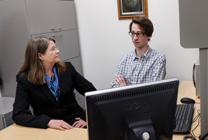 Ruth Daly sits at a computer with a student