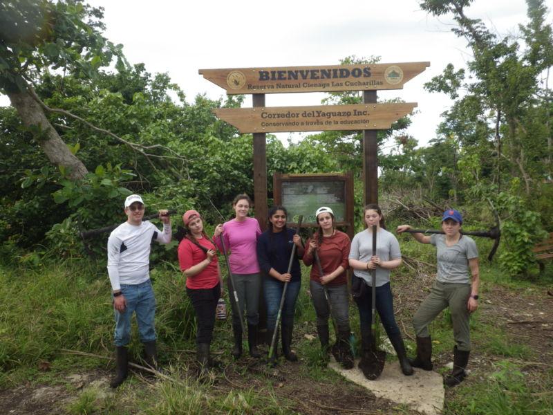 """Seven students pose under a sign that says """"Bienvenidos: Reserva Natural Cienaga Las Cucharillas"""""""