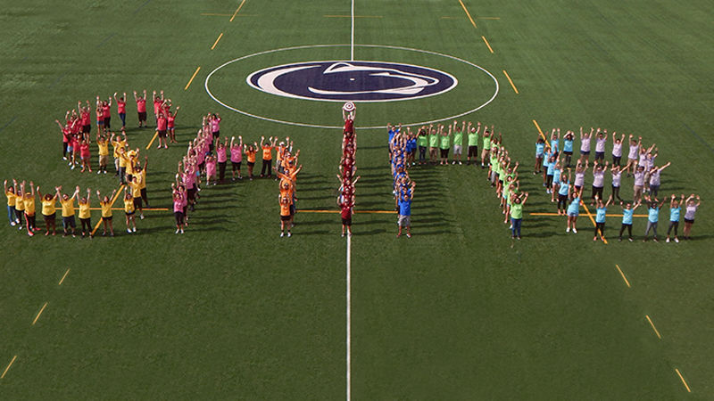 The Berks Orientation Team forming the word 'Shine' on the athletic field