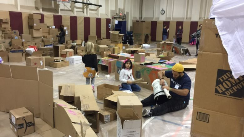 Photo of gymnasium filled with cardboard boxes and children playing