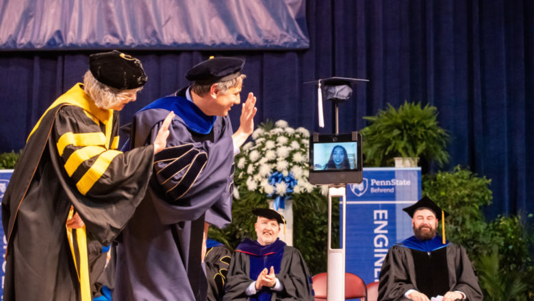 Two Penn State Behrend faculty members wave to a student whose face is on the monitor of a robot.