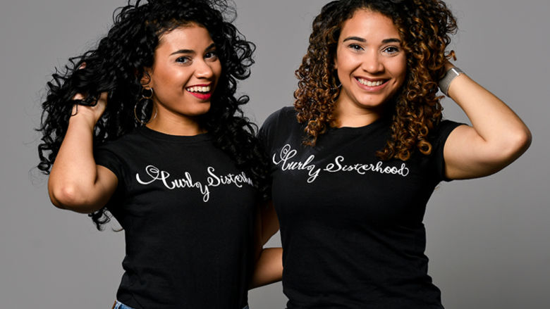 The Varona Sisters pose with their Curly Sisterhood t-shirts.