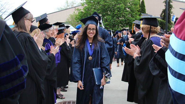Denise Castro, student marshal for the afternoon ceremony, leads the graduates through the reception line of faculty, staff, administrators, and platform party members celebrating their achievement.