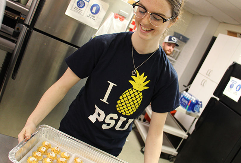 Student preparing food at Opportunity House
